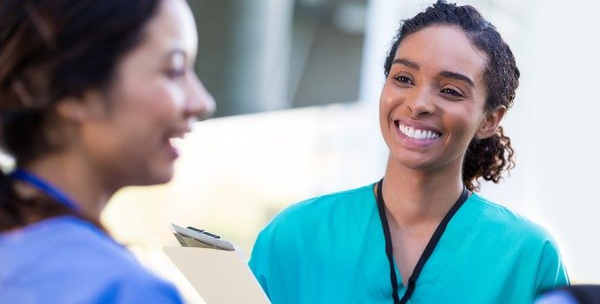 A female dental professional smiles at her peer