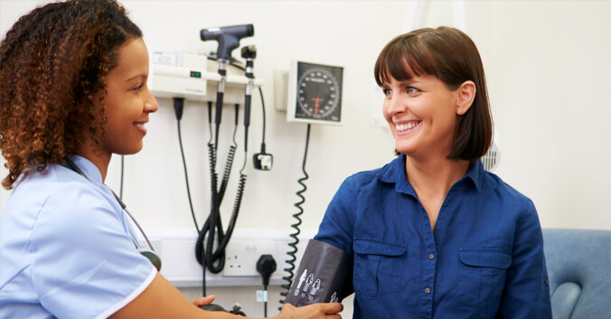 Staff member checks patient's blood pressure
