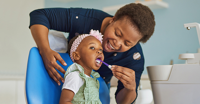 Mother brushes toddler's teeth