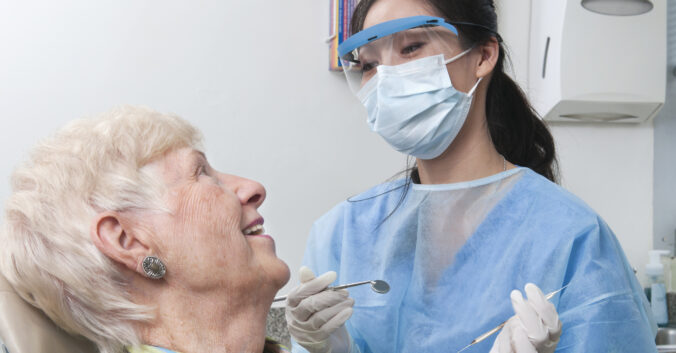 A female dental hygienist as she prepares to work on her teeth smiles and talks with a female patient