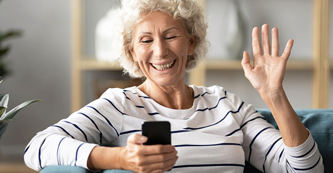A senior woman smiles and waves at a video call on her phone